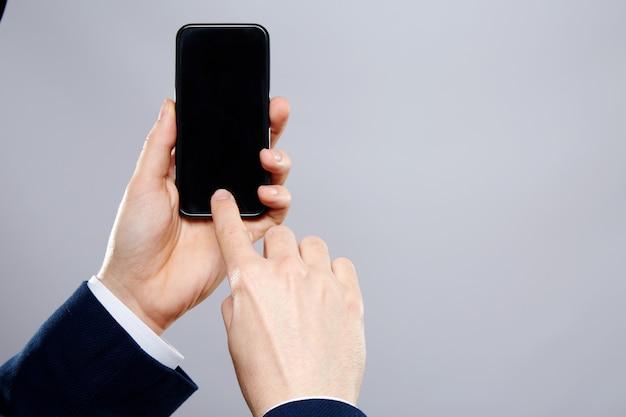 Mano del lavoratore che indossa una camicia bianca e parete del vestito, close up, concetto di affari, utilizzando il telefono cellulare, mock up
