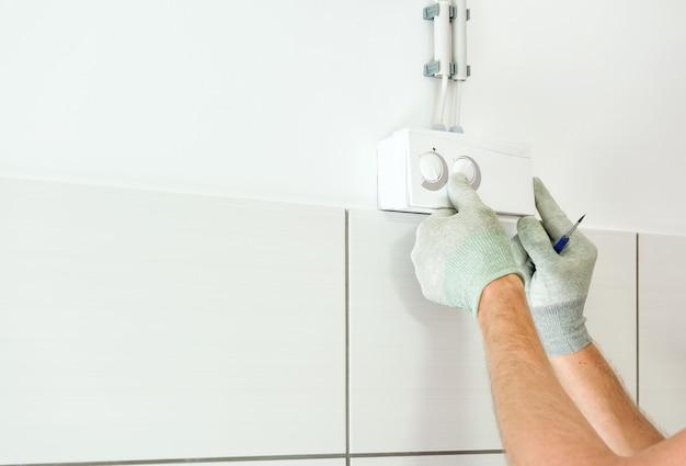 Le mani del lavoratore stanno collegando il sensore di umidità del sistema di ventilazione.