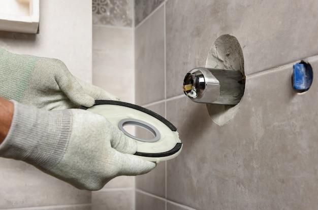 Le mani del lavoratore stanno montando un rubinetto incorporato