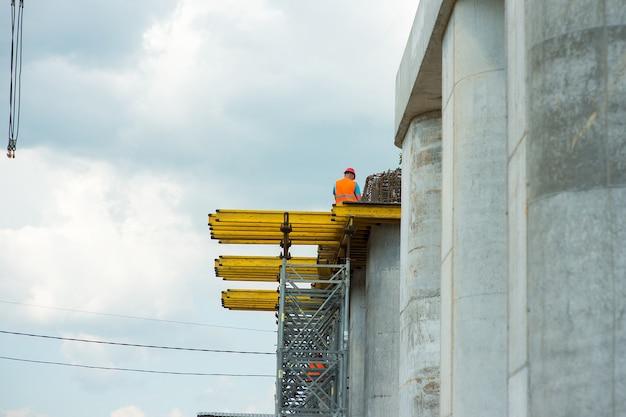 Lavoratore in un casco di sicurezza su colonne di cemento durante la costruzione di un ponte stradale