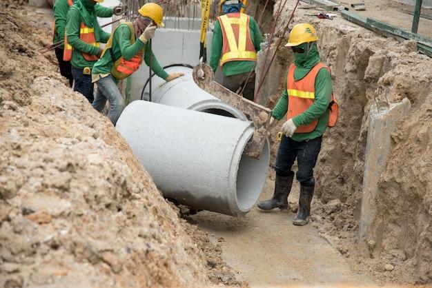 Il lavoratore in uniforme di sicurezza installa il drenaggio di tubi prefabbricati in calcestruzzo sotto terra