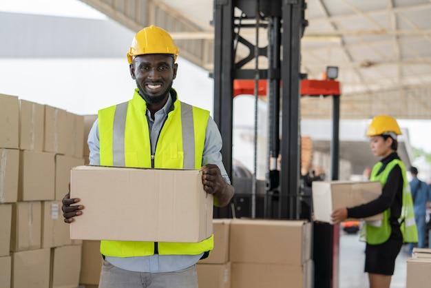 Lavoratore in giubbotto di sicurezza e casco tenendo la scatola di cartone