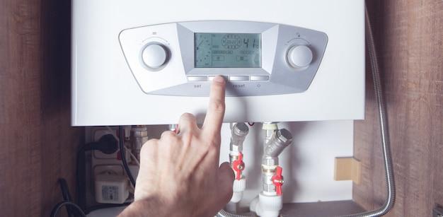 Il lavoratore ha installato la caldaia per il riscaldamento a gas centrale a casa