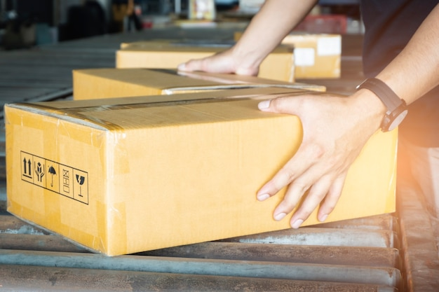 Scatole di cartone di smistamento del lavoratore sul nastro trasportatore.
