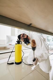 Lavoratore che spruzza ogni angolo con disinfettante