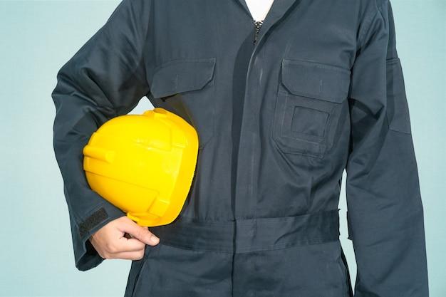 Lavoratore in piedi in tuta blu che tiene elmetto giallo isolato su sfondo blu