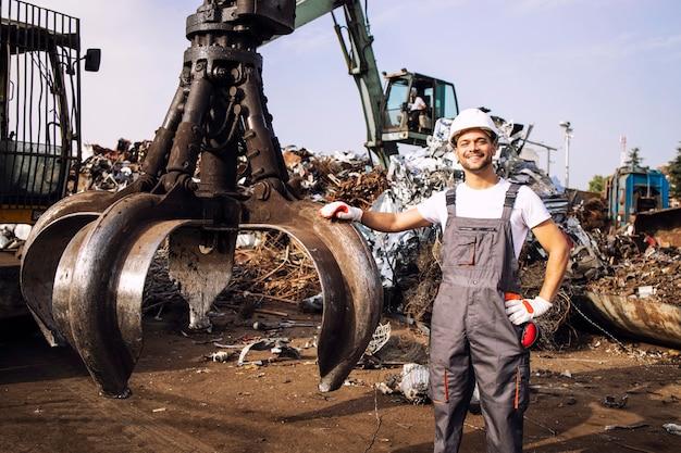 Lavoratore in piedi vicino alla macchina industriale idraulica utilizzata per il sollevamento di pezzi di metallo di scarto nel deposito di rifiuti
