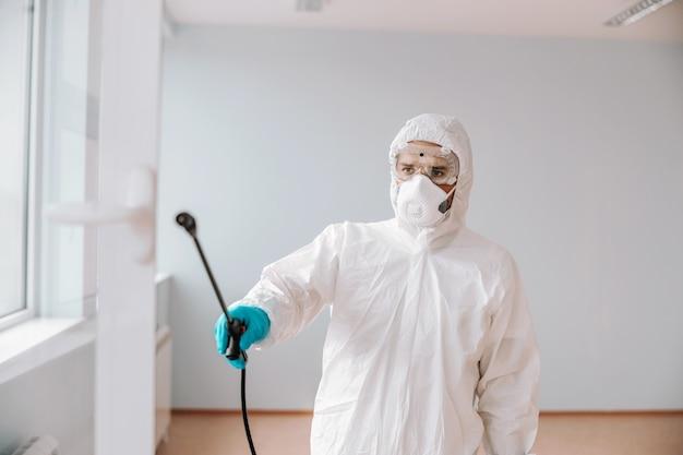 Lavoratore in uniforme sterile, con maschera e guanti che spruzzano con finestra disinfettante a scuola.