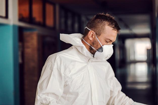 Lavoratore in uniforme bianca sterile in piedi nel corridoio a scuola dopo la disinfezione.