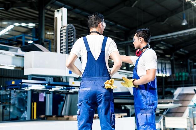 Gruppo di lavoratori in fabbrica che discute davanti alla macchina
