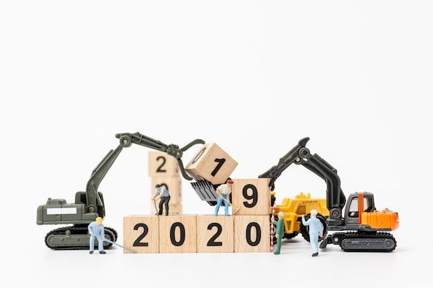 Le miniature delle squadre dei lavoratori creano blocchi di legno con il numero 2020