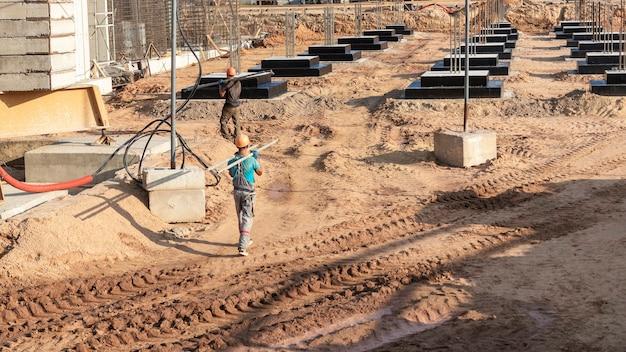 Un lavoratore trasferisce gli elementi per l'installazione della cassaforma in cantiere. cassaforma monolitica in calcestruzzo durante la costruzione di un edificio residenziale.