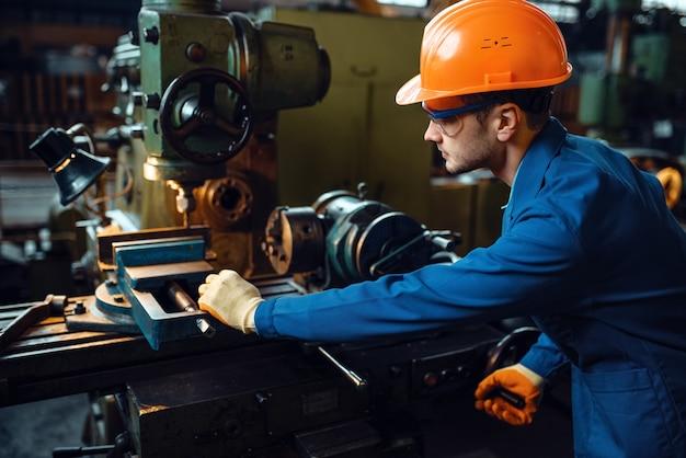 L'operaio in uniforme e casco lavora al tornio, pianta. produzione industriale, ingegneria della lavorazione dei metalli, produzione di macchine elettriche