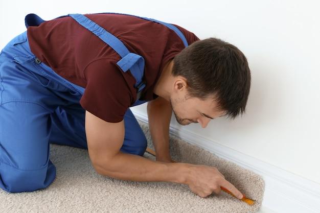 Lavoratore che utilizza la taglierina durante l'installazione di nuovi pavimenti in moquette in camera
