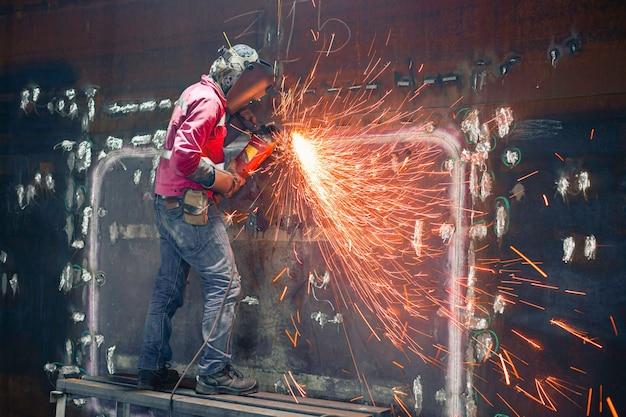 Lavoratore che utilizza la molatura a scintilla della ruota elettrica sulla piastra del guscio della parte in acciaio al carbonio del saldatore all'interno dello spazio limitato del serbatoio Foto Premium