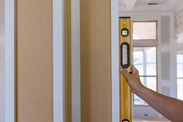 Il lavoratore che utilizza lo strumento di livellamento controlla le colonne di legno appropriate utilizzando il livello in costruzione