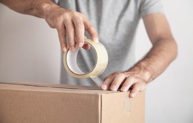 Lavoratore utilizzando nastro sigillante scatola di cartone