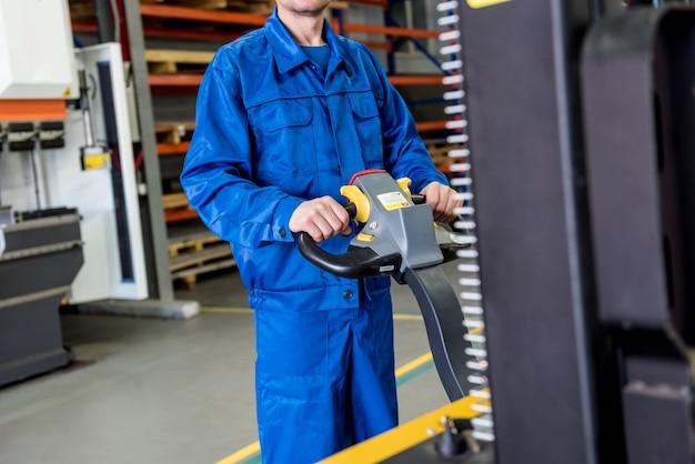 Un lavoratore in un magazzino utilizza un carrello elevatore manuale per trasportare i pallet.