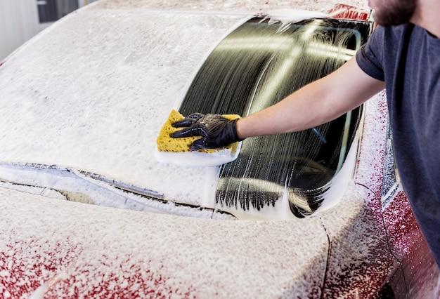 Operaio che lava automobile rossa con la spugna su un autolavaggio.
