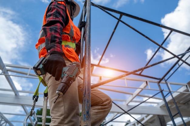 Lavoratore che indossa dispositivi di sicurezza e cinture di sicurezza che lavorano in altezza in cantiere.