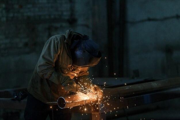Metallo di saldatura dell'operaio con scintille in fabbrica.