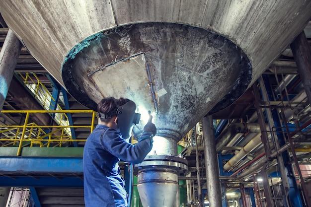 La saldatura dell'operaio ripara il serbatoio inferiore del silo inossidabile utilizzando il saldatore tig