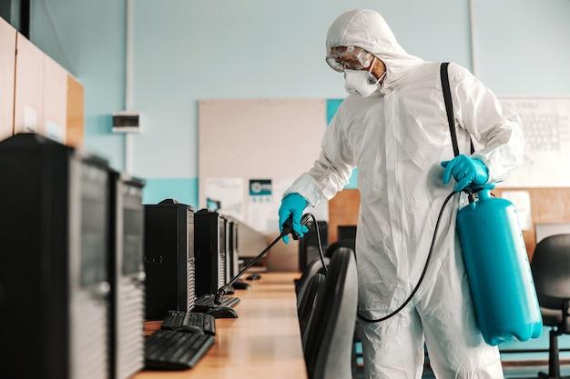 Lavoratore in uniforme bianca sterile, con guanti di gomma e maschera sulla tenuta dello spruzzatore con armadio informatico disinfettante e sterilizzante a scuola.