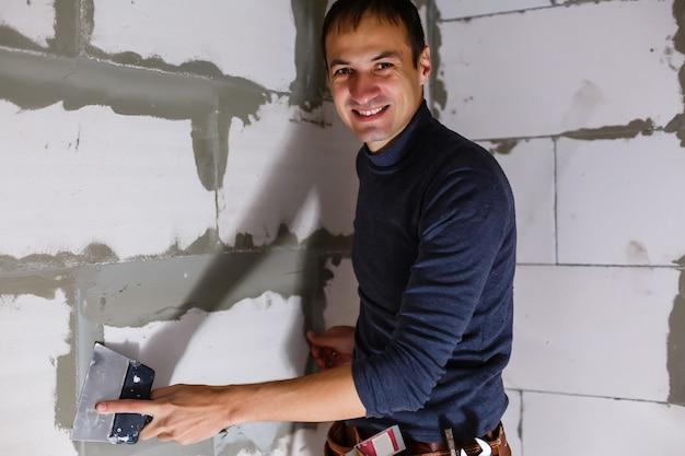 L'operaio pulisce le cuciture fuori dalla casa di mattoni. il costruttore elabora la muratura. muratore del muratore della costruzione che installa mattone rosso con la spatola della cazzuola all'aperto.