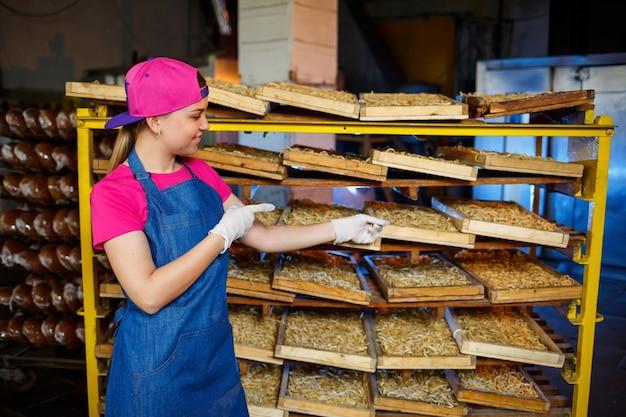 Operaio con una scatola di pasta. la ragazza lavora alla produzione di spaghetti. fare le tagliatelle. pastificio.