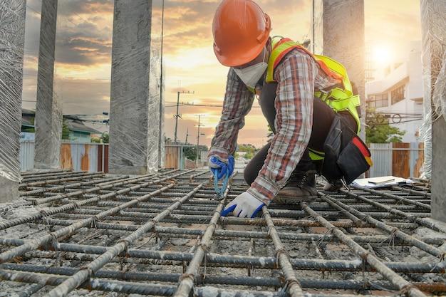 Operaio con linee di costruzione in ferro per la costruzione di fondamenta, operaio edile