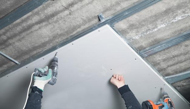 Lavoratore con un trapano avvitatore torce la vite nel muro a secco.