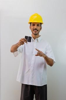 Operaio con il casco che tiene un pannello solare fotovoltaico isolato su priorità bassa bianca.