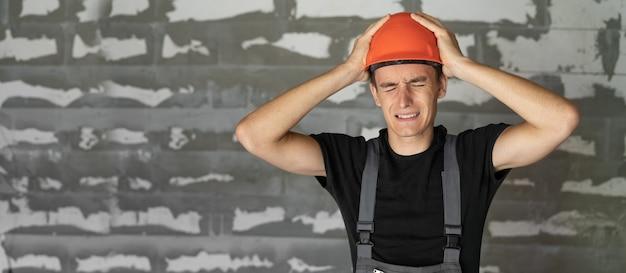 Operaio con casco casco arancione vicino a un muro di pietre. si prese la testa con le mani. copia spazio