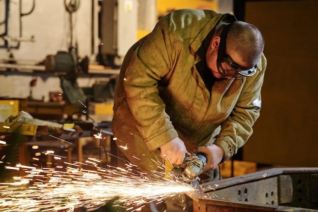Operaio con maschera protettiva che salda metallo e scintille in fabbrica