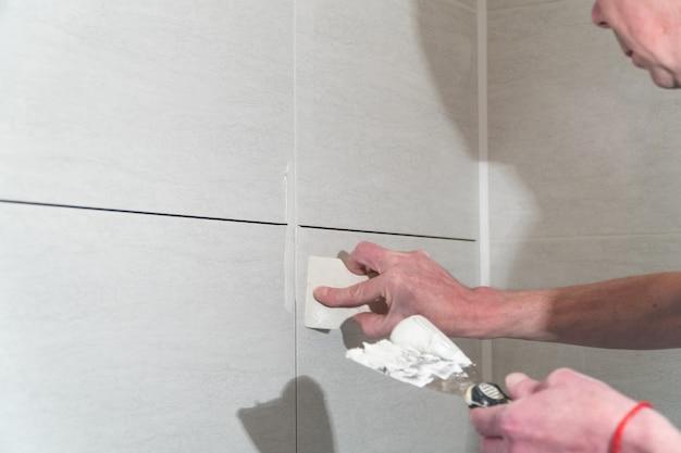 L'operaio con una spatola di gomma riempie le cuciture con una soluzione la tecnologia di posa delle piastrelle