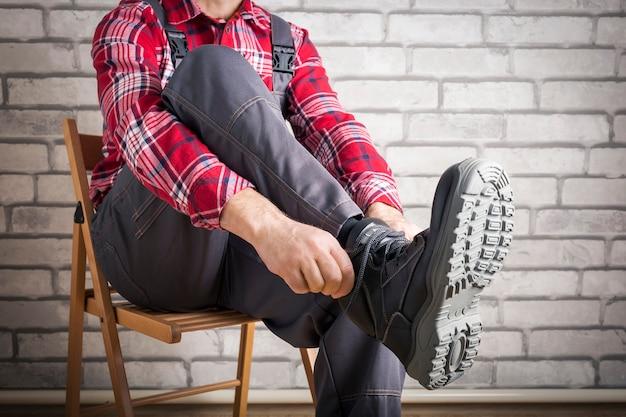 Un lavoratore con scarpe antinfortunistiche. indumenti di protezione del costruttore. lavoro di sicurezza.
