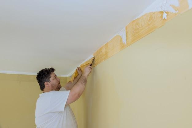 Operaio con l'utilizzo di un raschietto per rimuovere una ristrutturazione del luogo di carta da parati a casa.