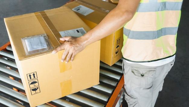 Lavoratore che lavora su un nastro trasportatore, le sue scatole di cartone di smistamento per la consegna a un cliente. magazzino di distribuzione, pacchi, merci di spedizione,