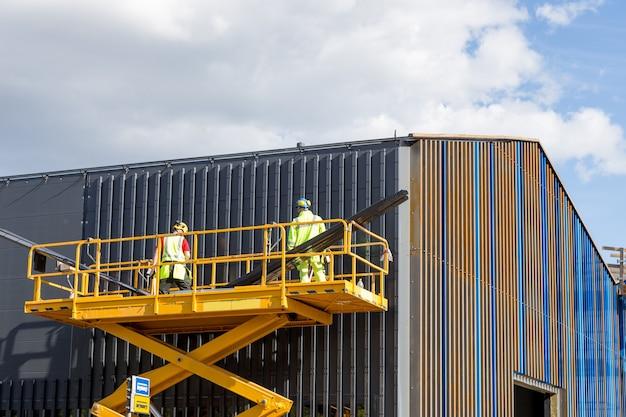 Lavoratori sulla piattaforma di lavoro aereo durante i lavori di installazione della facciata