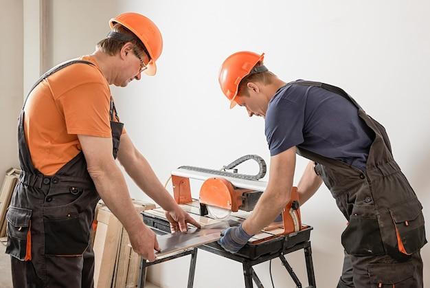 Gli operai stanno tagliando una piastrella di ceramica su una sega da taglio a umido