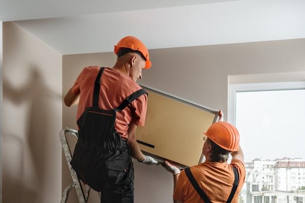I lavoratori stanno installando un sistema split per un sistema di condizionamento domestico.