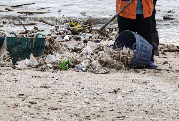 Lavoratori che puliscono spiaggia da immondizia.