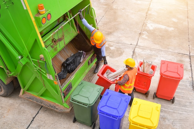 I lavoratori raccolgono i rifiuti con il camion della raccolta dei rifiuti, lavoratori della raccolta dei rifiuti in un'area residenziale