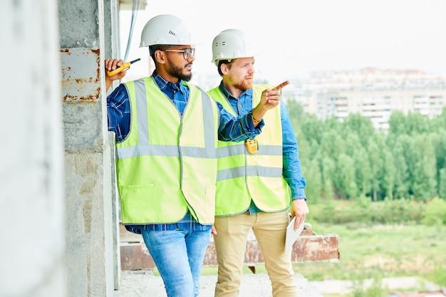Lavoratori che discutono della posizione dell'edificio moderno