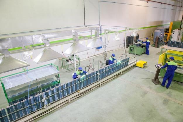 Operai in fabbrica in officina impegnati nella saldatura e brasatura di tubi in rame ai radiatori Foto Premium
