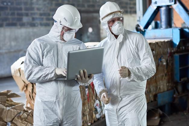 Lavoratori in abiti hazmat nella moderna fabbrica di riciclaggio