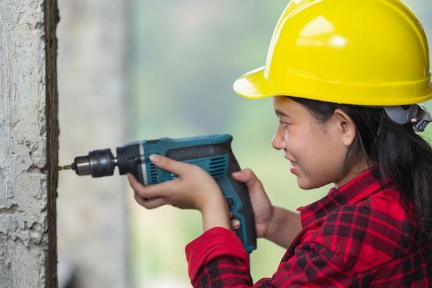 Lavoratori che tengono trapano elettrico in cantiere, concetto di festa del lavoro