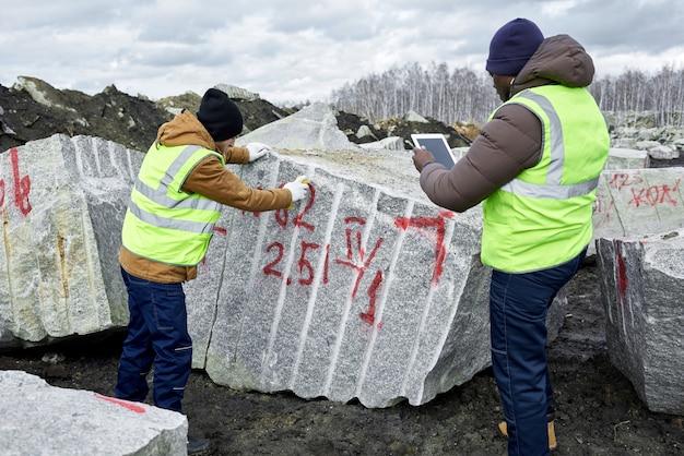 Lavoratori che contrassegnano i blocchi di granito