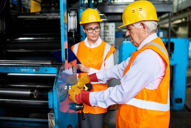 Lavoratori che fanno funzionare le macchine alla fabbrica moderna