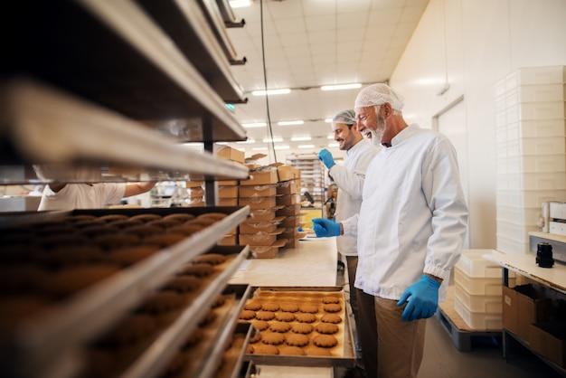 Lavoratori che imballano i biscotti in scatole mentre stavano nella fabbrica alimentare.